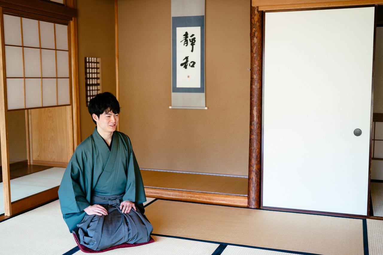 Ryo Iwamoto sitting with his legs holded in the corner of a tatami room in his tea house