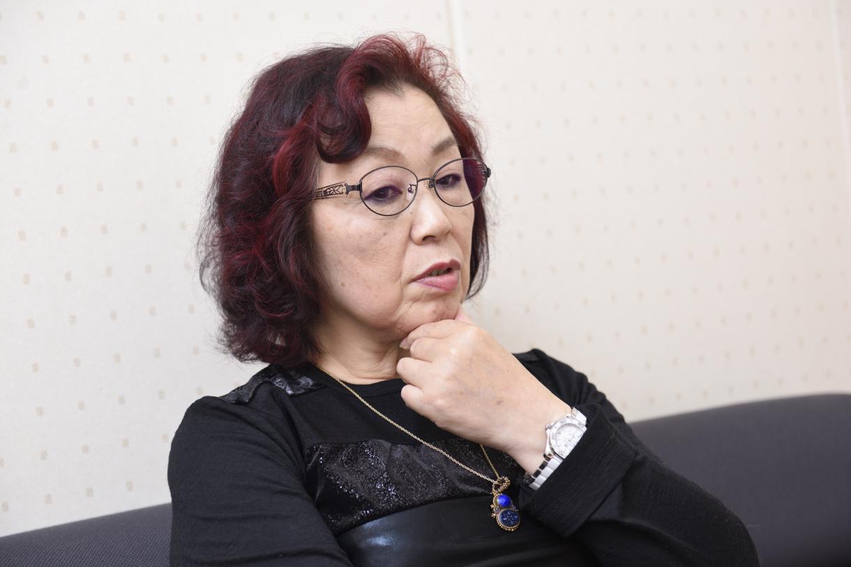 Sayoko Nobuta, stroking her chin as she thinks